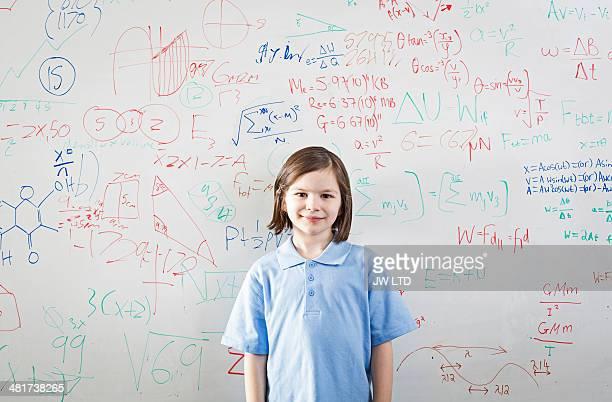schoolgirl in front of wipe board, math equations