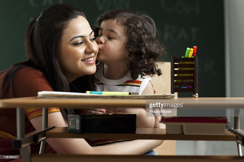 Schoolgirl (2-3) kissing teacher : Stock Photo