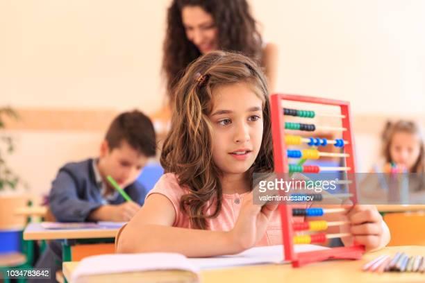 schulmädchen lernen mathematik im klassenzimmer - grundschule stock-fotos und bilder