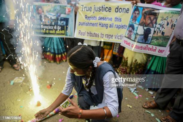 Schoolgirl lights firecrackers as she celebrates along with others after police personnel shot dead four detained gang-rape and murder suspects in...