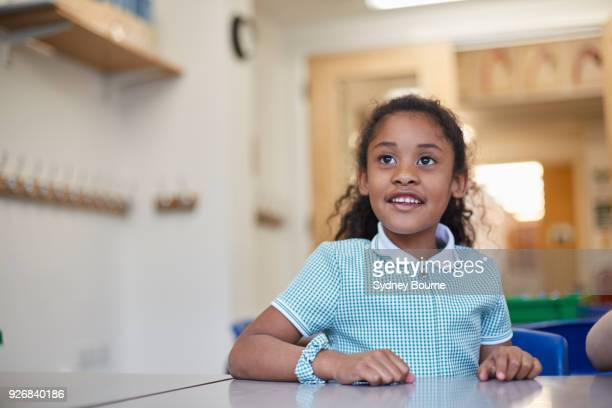 schoolgirl listening in classroom lesson at primary school - schoolgirl stock pictures, royalty-free photos & images