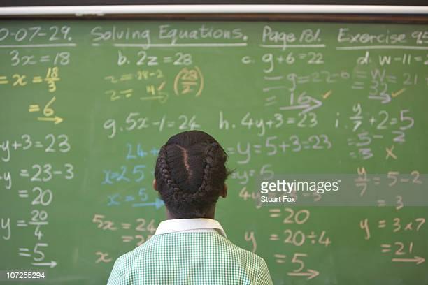 Schoolgirl looking at chalkboard with algebra sums, KwaZulu Natal Province, South Africa