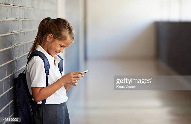 schoolgirl looking at phone and smiling - solo una bambina femmina foto e immagini stock