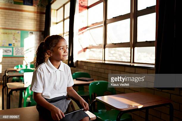 schoolgirl looking out of window of classroom - education stock pictures, royalty-free photos & images