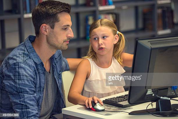 Schoolgirl on computer with father