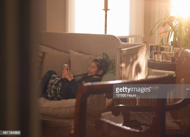 A schoolgirl on the sofa looking at her phone