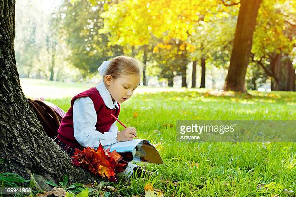 schoolgirl outdoors - workbook stock photos and pictures