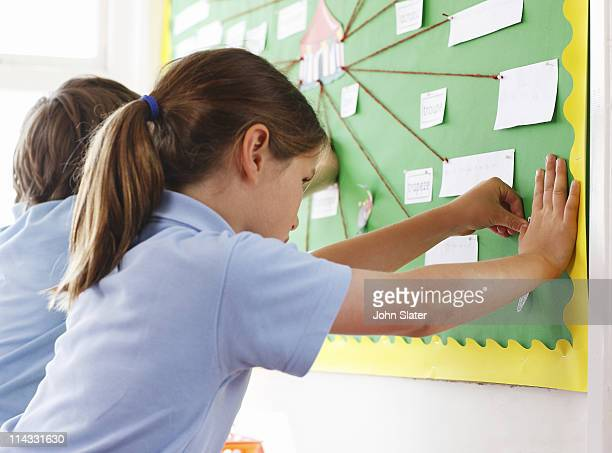 schoolgirl pinning item to pin board
