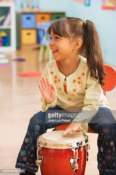Schoolgirl (4-5) playing conga in classroom, smiling