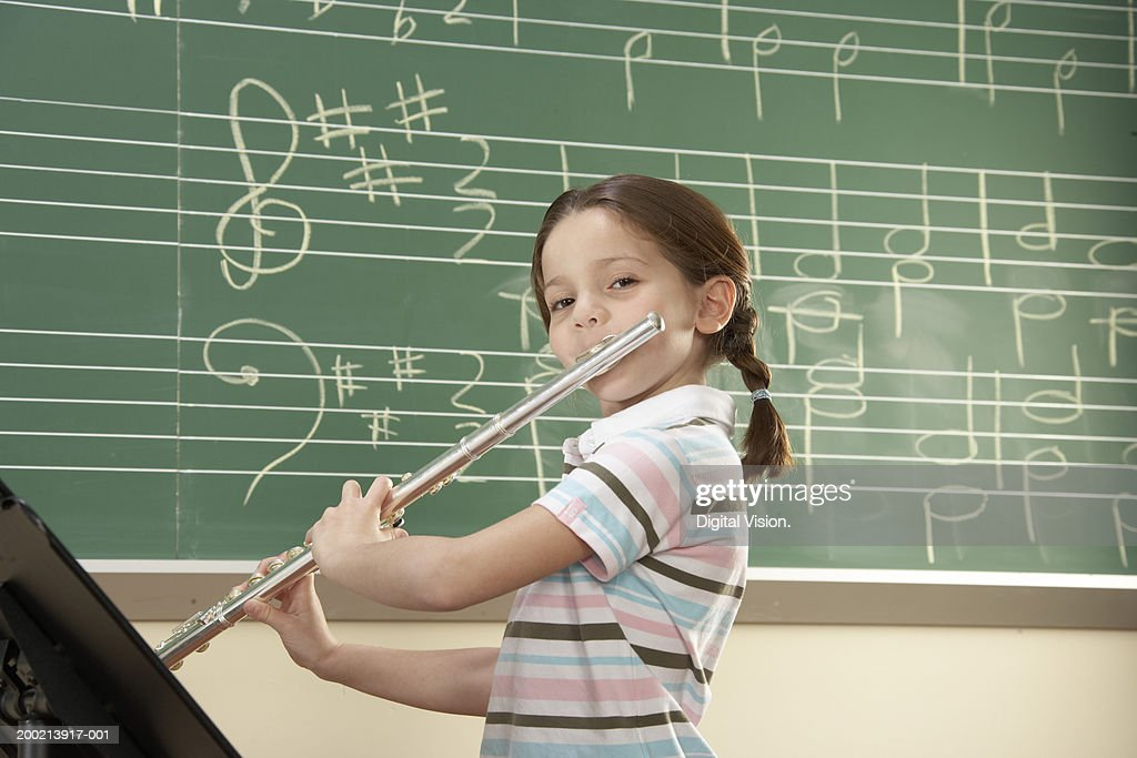 Schoolgirl (5-10) playing flute, smiling, portrait : Stock-Foto