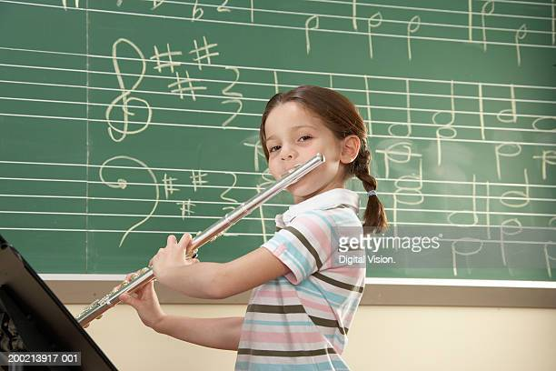 Schoolgirl (5-10) playing flute, smiling, portrait