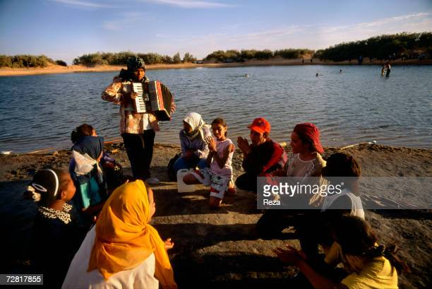 A schoolgirl plays the accordion during a picnic by Ein Dabban Lake April 2000 in Ein Dabban Lake Libya