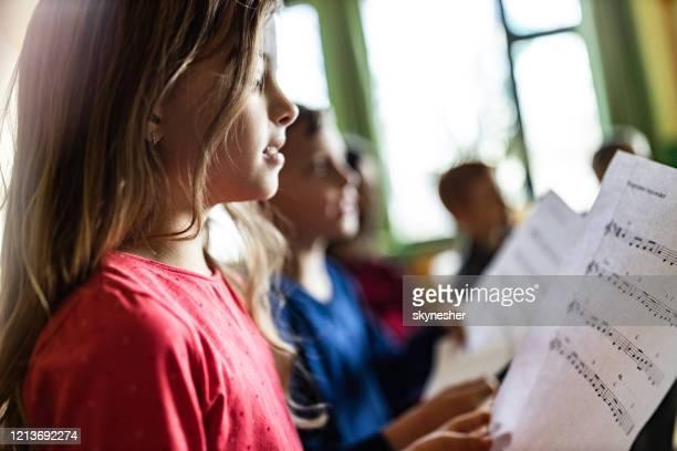 schoolmeisje dat met bladmuziek op een klasse op school oefent. - alleen kinderen stockfoto's en -beelden