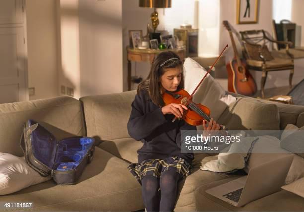 Schoolgirl practising the violin, using a laptop