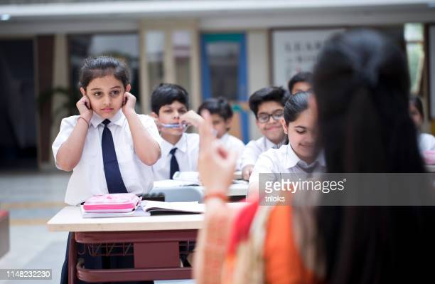 schoolgirl pulling her ears in class - penalty stock pictures, royalty-free photos & images
