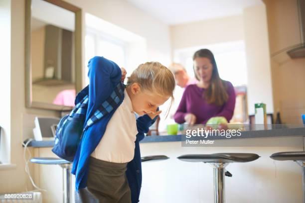 schoolgirl putting on school satchel in kitchen - preparation stock pictures, royalty-free photos & images
