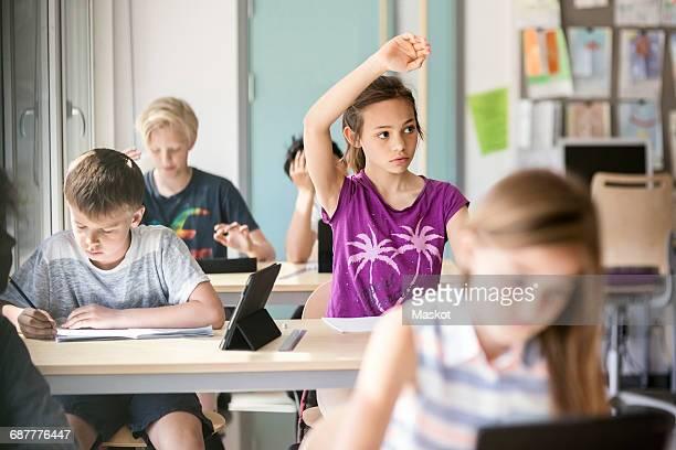 Schoolgirl raising hand at desk in classroom