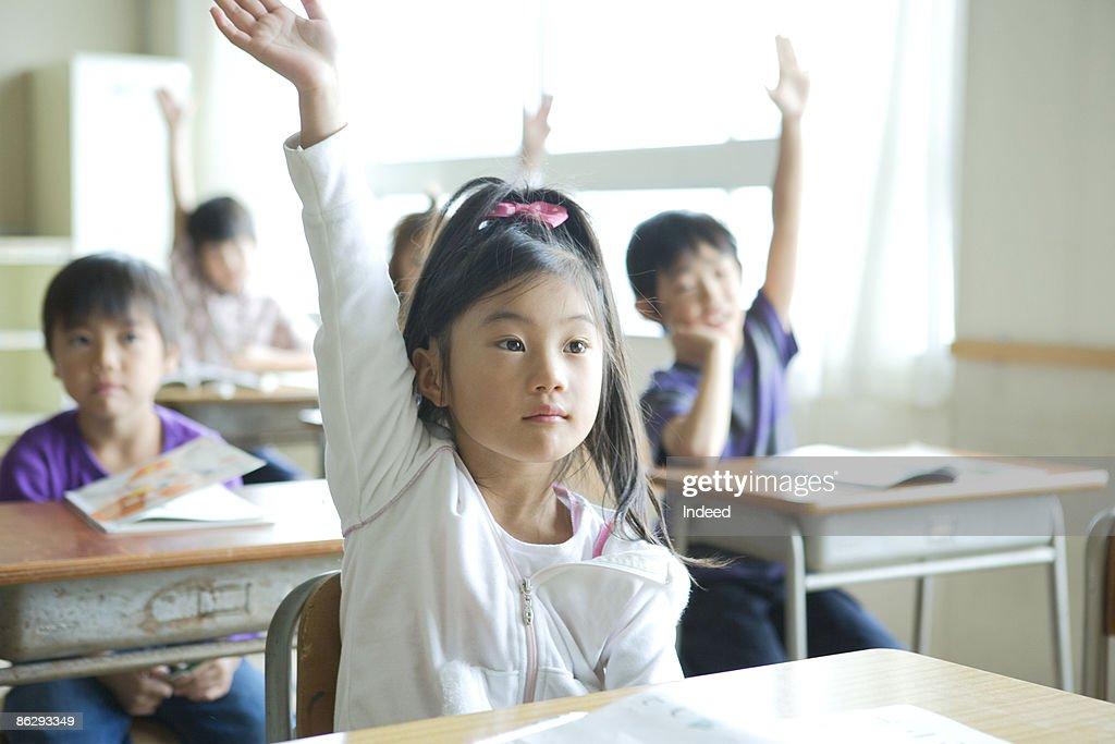 Schoolgirl (8-9) raising her hand : ストックフォト
