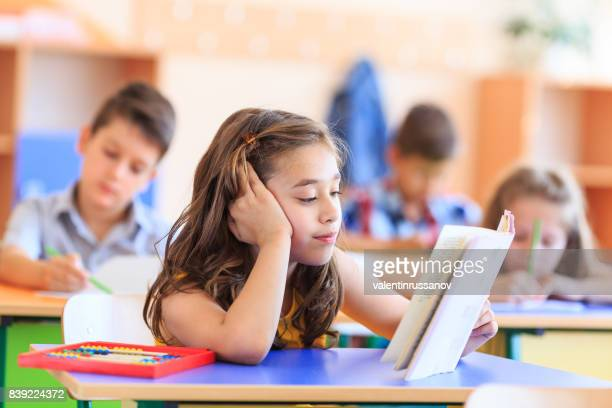 schoolgirl reading a book in the classroom - kids reading in classroom stock pictures, royalty-free photos & images
