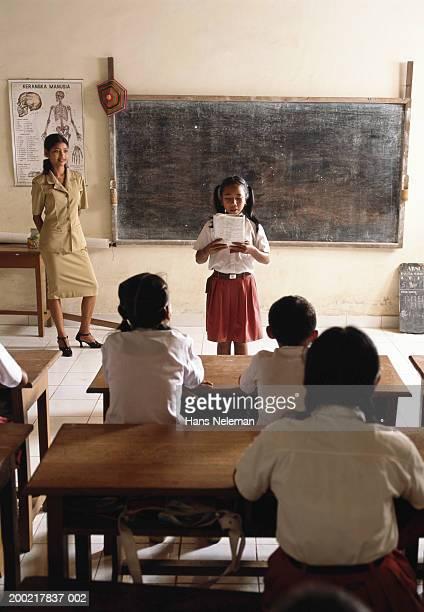 Schoolgirl (8-10) reading in front of class