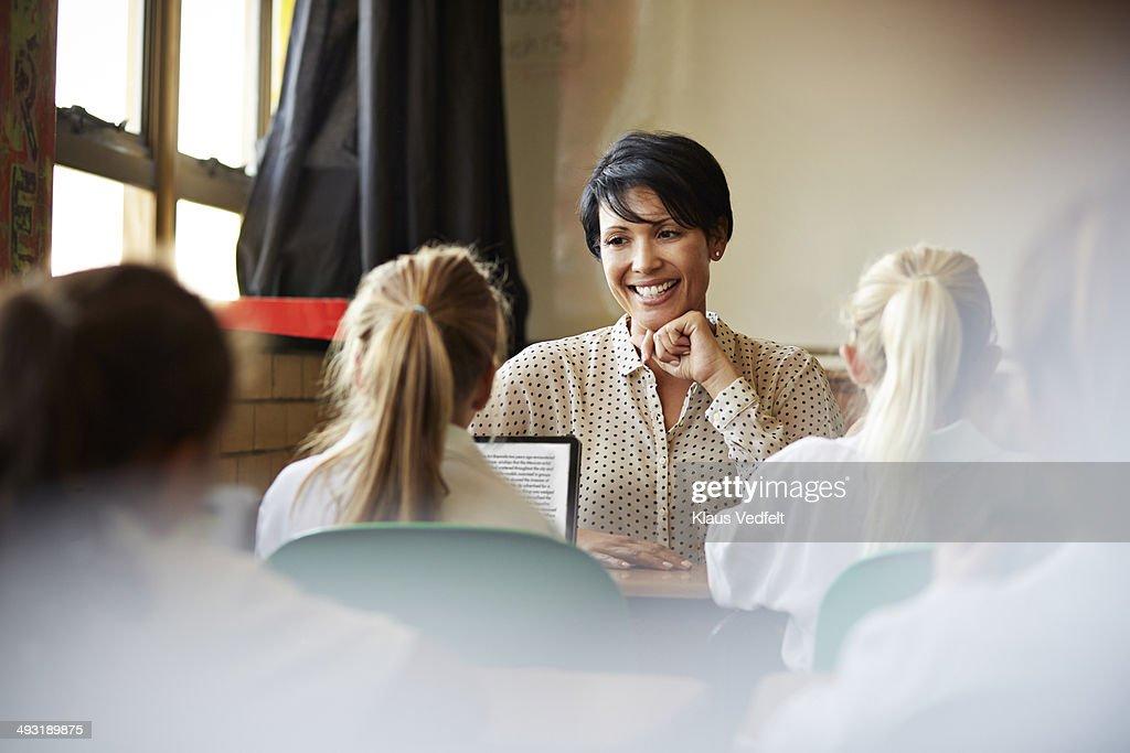 Schoolgirl reading on tablet for teacher in class : Stock Photo