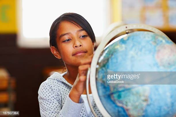 Schoolgirl reading the world globe