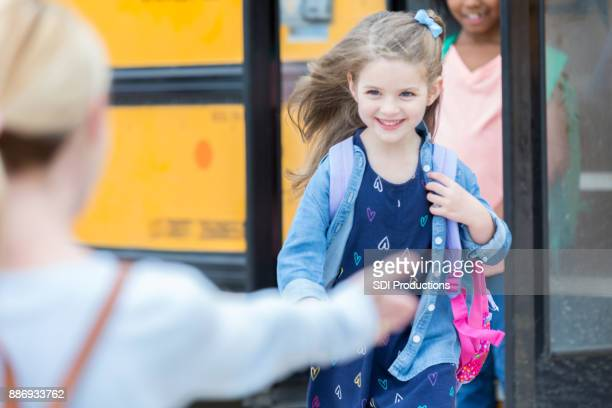schoolgirl runs into her mothers arms after school - first day of school stock pictures, royalty-free photos & images