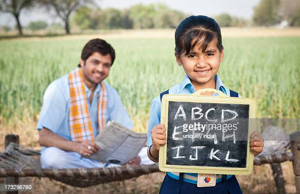 Schoolgirl showing a slate with his father sitting in the background, Sohna, Haryana, India