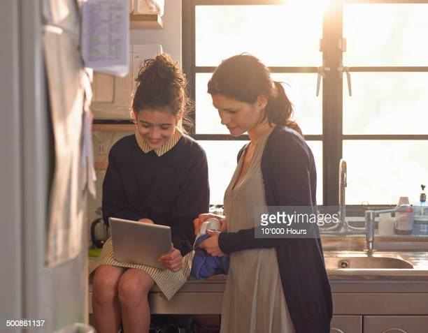 A schoolgirl showing her mother content on an ipad