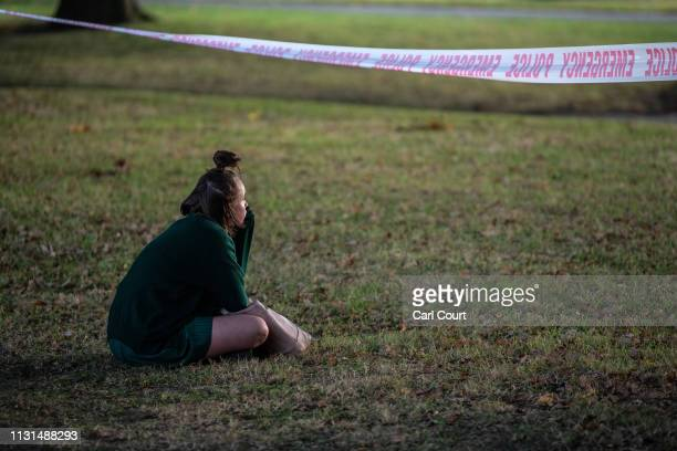 A schoolgirl sits beneath police tape marking a cordon as she looks towards Al Noor mosque on March 19 2019 in Christchurch New Zealand 50 people...