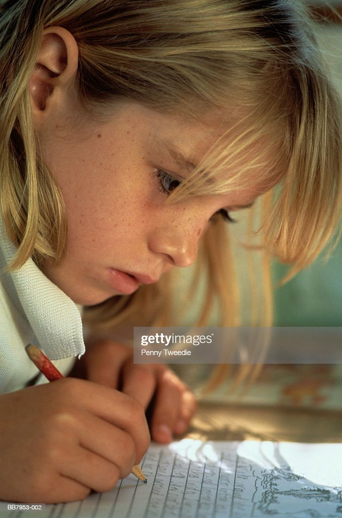 Schoolgirl (8-10) sitting at desk, writing, close-up : Stock Photo