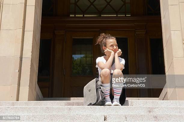 Schoolgirl sitting on school steps