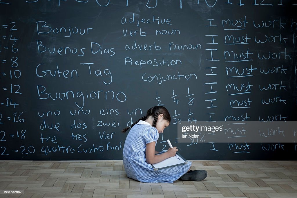 Schoolgirl sitting studying in front of large chalkboard with schoolwork chalked on it : Stock Photo