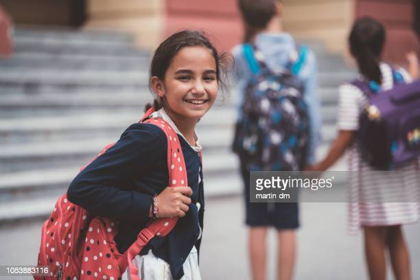schoolgirl smiling to camera - first day of school stock pictures, royalty-free photos & images