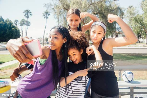 schoolgirl soccer players taking smartphone selfie on school sports field - california strong stock photos and pictures