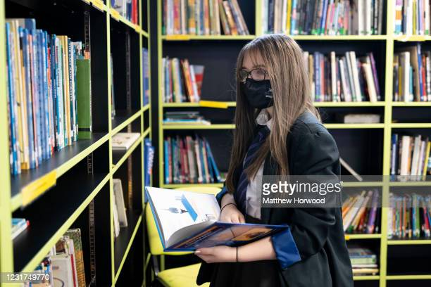 Schoolgirl takes a book from the library at Willows High School on March 16, 2021 in Cardiff, Wales. Secondary schools in Wales reopen this week...