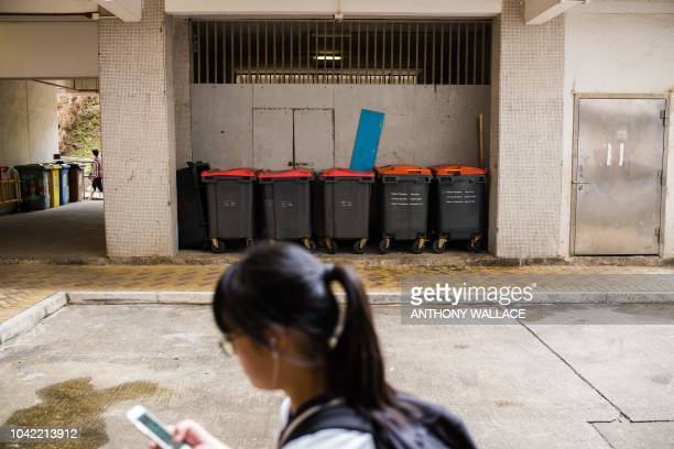 A schoolgirl uses her phone as she walks past large rubbish skips at the Choi Wan public housing estate in Hong Kong on September 28 where there were...