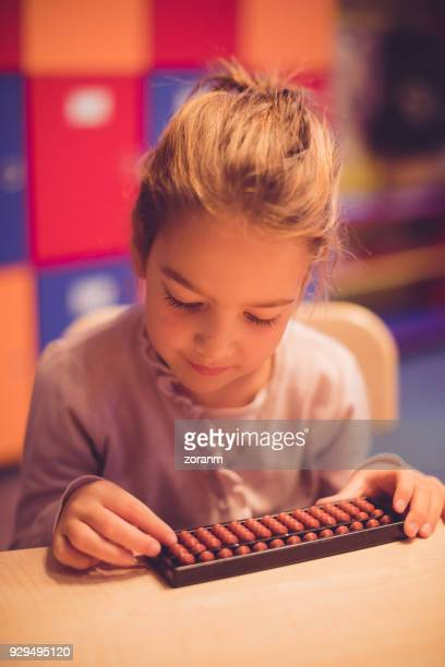 Schoolgirl using abacus to calculate