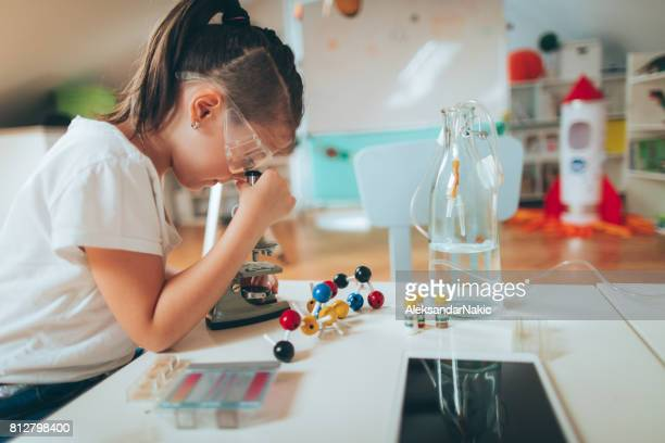 Schoolgirl using microscope in classroom