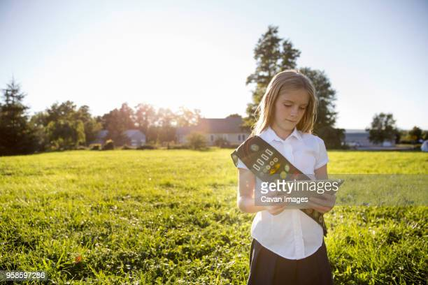 schoolgirl using tablet computer while standing on grassy field - sash stock pictures, royalty-free photos & images