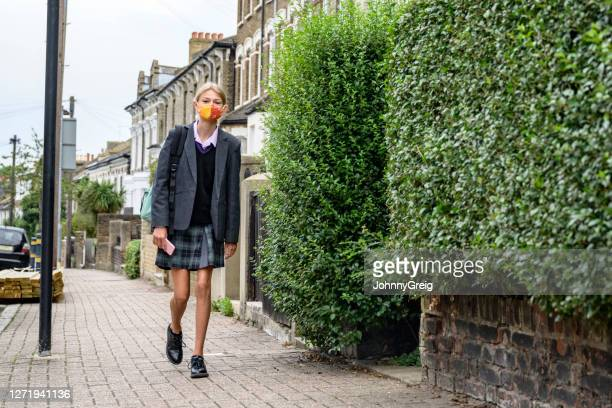 schoolgirl walking to school wearing face mask - uniform stock pictures, royalty-free photos & images