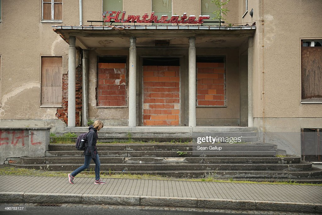 A schoolgirl walks past a shuttered movie theatre on May 14, 2014 in Seifhennersdorf, Germany. Seifhennersdorf is going into a decline that has hit its economy and in which its population has dropped from 6,874 in 1990 to 3,935 in 2012. The state of Saxony officially closed the Seifhennersdorf Middle School in 2012 after only 38 students registered, two short of the 40 the state required to keep the school open. Rather than agree to the school's closing, a group of parents and other volunteers have since assumed the duties of teachers and staff themselves and are trying to get recognition of their 'illegal' school through a court case that now lies with Germany's Federal Constitutional Court. Eleven 6th graders attend the school, even though the state does not recognize their enrollment. School closings across Germany have reached epidemic proportions with 6,100 closures between 2003 and 2013, due in large part to Germany's low birth rate, a phenomenon typical across much of Europe. In Saxony the low birth rate has combined with a steady migration of young people to big cities and to western Germany and the number of schoolchildren has fallen by close to 50% and led to the closure of 1,000 out of a total of 2,500 state schools since 1989.