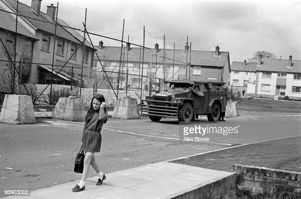 A schoolgirl walks past an armoured car parked outside a barricaded British Army base on the Republican Lenadoon Estate in west Belfast 12th April...