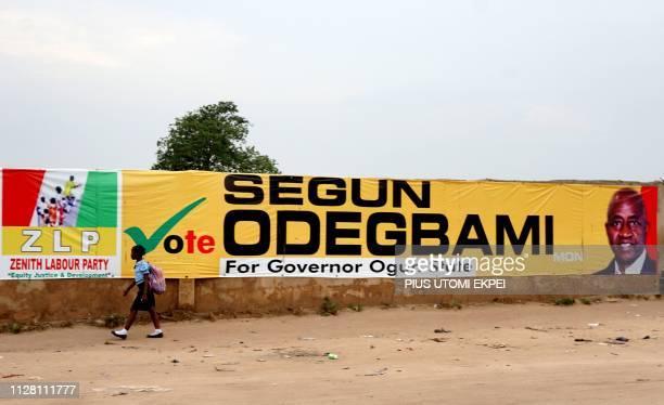 A schoolgirl walks past long campaign banner bearing photograph of former captain of Nigerian national football team the Super Eagles Segun Odegbami...