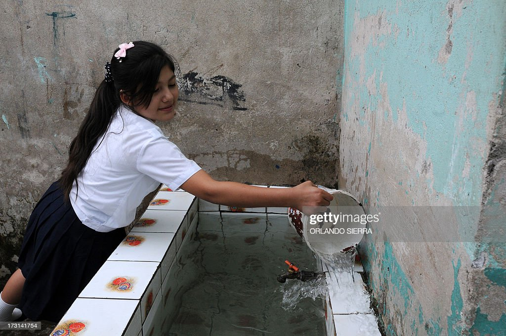A schoolgirl washes a drinking fountain at her school as part of a Health Ministry campaign focused on mosquito control in order to combat dengue fever, a disease caused by four strains of virus that are spread by the mosquito Aedes aegypti, in Tegucigalpa on July 8, 2013. Authorities have issued dengue alerts in four nations across Central America, where alarm is rising as the mosquito-borne disease has infected 30,000 people and killed 17 this year alone. The illness can be fatal, developing into hemorrhagic fever, which can lead to shock and internal bleeding. AFP PHOTO / Orlando SIERRA