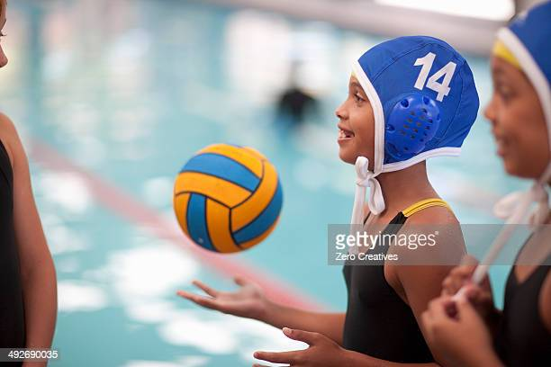 Schoolgirl water polo players poolside with ball