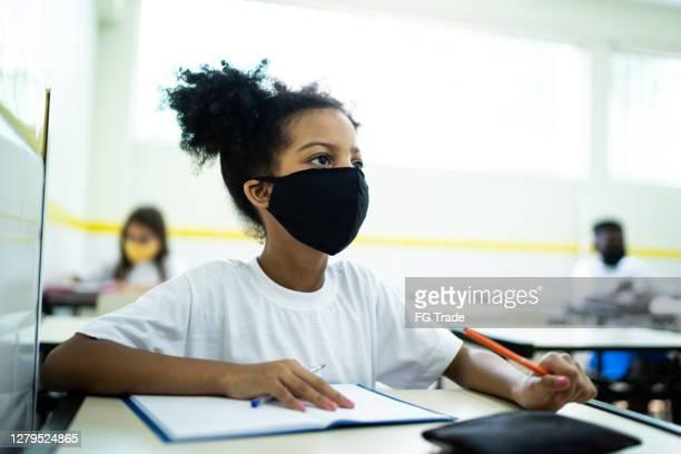 aluna usando máscara facial estudando em sala de aula - pandemia - fotografias e filmes do acervo