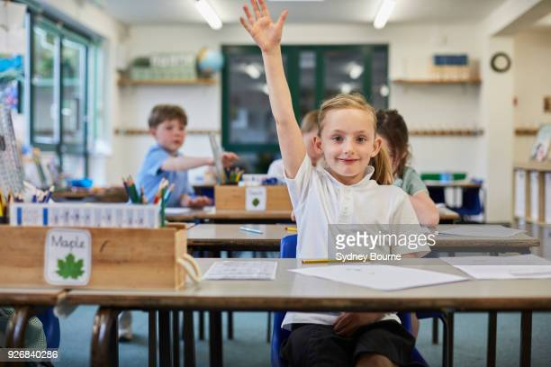 schoolgirl with hand raised in classroom at primary school - 10歳から11歳 ストックフォトと画像