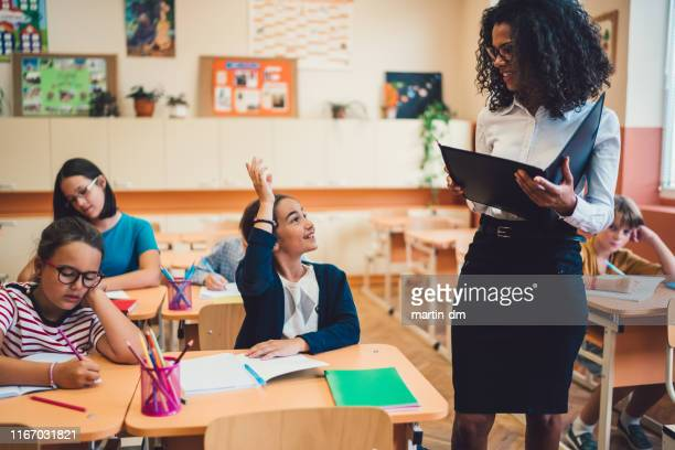schoolgirl with hand raised wants to answer teacher's question in class - school principal stock pictures, royalty-free photos & images