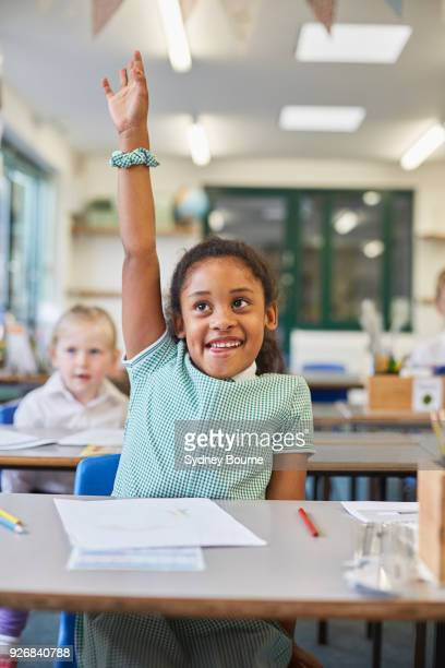 schoolgirl with hand up in classroom at primary school - hand raised stock pictures, royalty-free photos & images